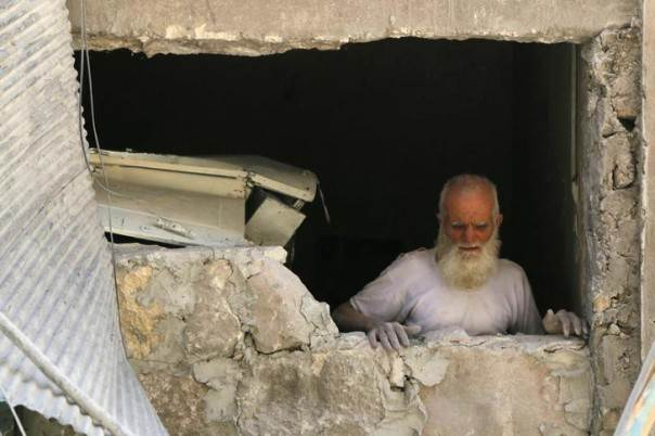 A man stands near damaged buildings caused by what activists say was shelling by forces loyal to Syria's President Bashar al-Assad, in Aleppo's countryside May 21, 2014. REUTERS/Jalal Al-Mamo