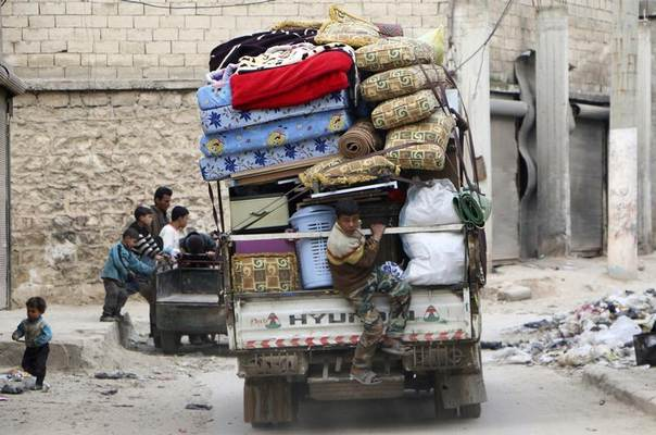 A boy sits at the back of a pick-up truck loaded with belongings as he flees with his family the violence in Aleppo's al-Jazmati district February 10, 2014. REUTERS/Hosam Katan