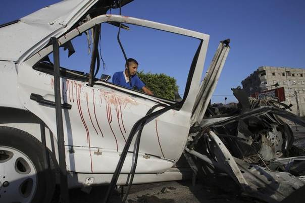 Bloodstains are seen as a Palestinian boy looks at the remains of a car which police said was hit in an Israeli air strike in Rafah in the southern Gaza Strip July 16, 2014. REUTERS/Ibraheem Abu Mustafa