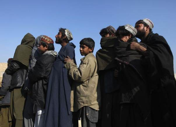 Afghan men line up to receive winter aid, donated by Muslim Hands, a U.K.-registered international aid organization, in Kabul January 5, 2014. REUTERS/Mohammad Ismail