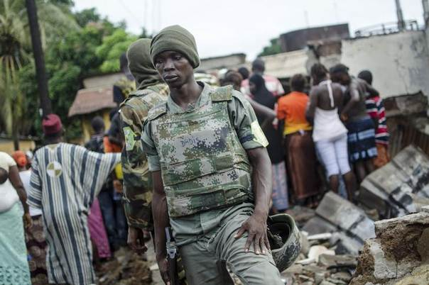 Soldiers stand on the remains of a house that was burnt down during pre-election communal violence in the Taouyah neighbourhood of Guinea's capital Conakry, September 25, 2013. REUTERS/Tommy Trenchard/