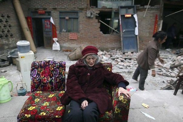 An elderly woman sits on a sofa in front of damaged houses