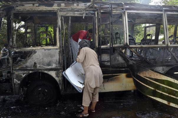 A rescue worker and security official collect evidence from a burned bus at the site of a bomb blast in Quetta, Pakistan, June 15, 2013. REUTERS/Naseer Ahmed