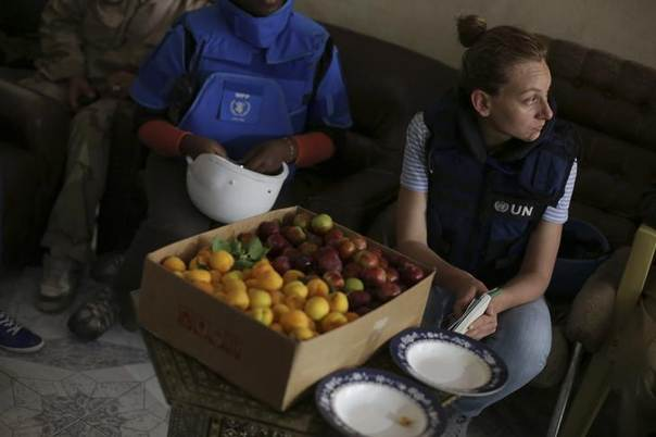 United Nations and World Food program members sit beside a box of fruits in eastern Ghouta of Damascus, May 24, 2014 REUTERS/Bassam Khabieh