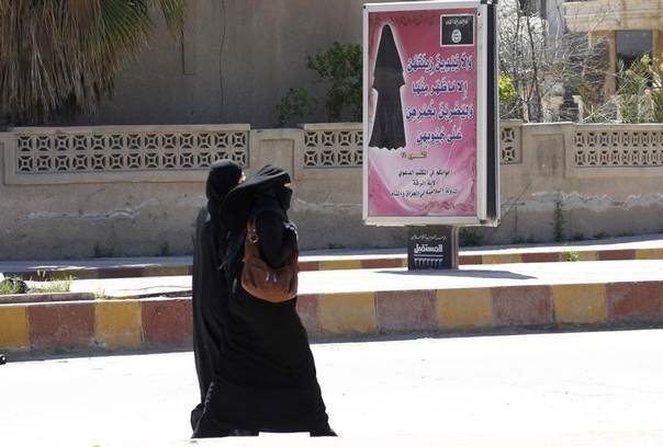 A sign (in white) by the Islamic State is seen in the city of Mosul July 21, 2014 REUTERS/Veiled women walk past a billboard that carries a verse from Koran urging women to wear a hijab in the northern province of Raqqa, Iraq, March 31, 2014. REUTERS/Stringer