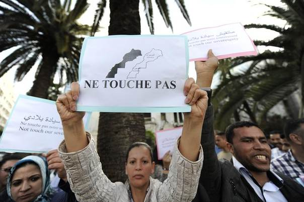 Moroccans hold signs during a protest against U.S.-backed plans to broaden the mandate of UN peacekeepers in the disputed Western Sahara, in Casablanca April 22, 2013. The sign reads,