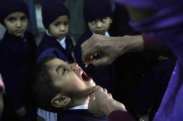 A female polio worker gives polio vaccine drops to a child in Lahore December 20, 2012. REUTERS/Mohsin Raza