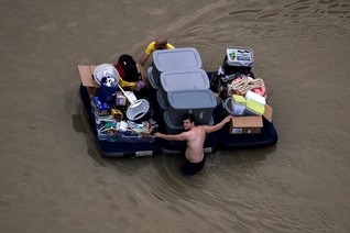 Residents wade with their belongings through flood waters brought by Tropical Storm Harvey in Northwest Houston