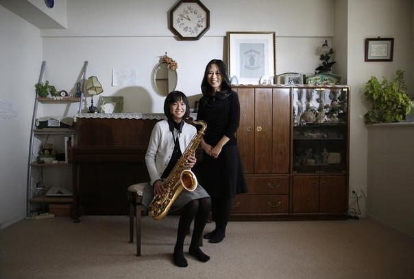 Manami Miyazaki (R), 39, and her daughter Nanaha, 13 and holding her alto saxophone, pose for a photograph at their home in Tokyo, Japan February 3, 2014.   Manami, who is a housewife, studied until she was 20. Her ambition was to work somewhere where she could meet lots of people. She hopes that her daughter will build a loving home with a happy marriage.   Manami says it would be great if her daughter could find work that makes use of her abilities and interests. Nanaha wants to be either a designer, musician or a nurse.