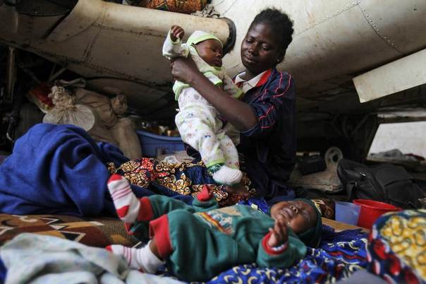 A Central African woman displaced by inter-communal violence in the country takes care of her twin baby boys at a camp for displaced persons at Bangui M'Poko International Airport February 11, 2014. REUTERS/Luc Gnago