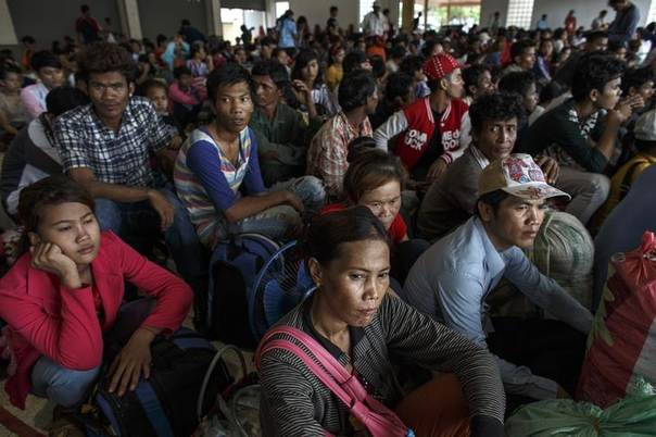 Cambodian workers wait for their documents to be processed at the Aranyaprathet police station as they prepare to move back to Cambodia in Sa Kaew June 15, 2014 REUTERS/Athit Perawongmetha