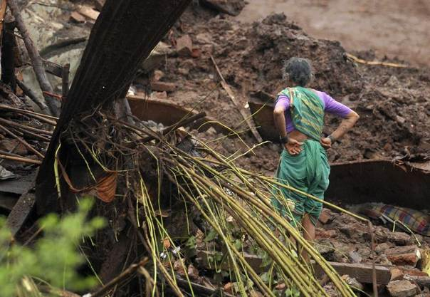 A resident looks at the debris of her damaged house after a landslide at Malin village in the western Indian state of Maharashtra, July 30, 2014. REUTERS/Stringer