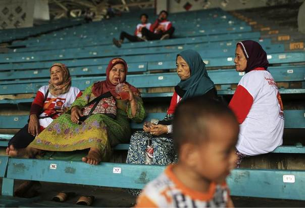 Women attend a campaign rally of the Great Indonesia Movement Party at a stadium in Jakarta March 23, 2014. REUTERS/Beawiharta