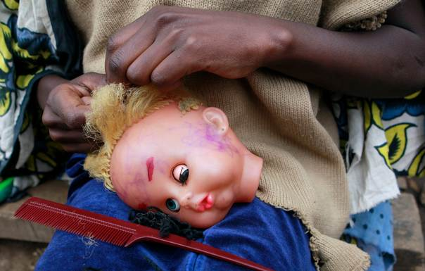 In a 2011 photo, a girl plaits her doll's hair outside her house in Kibera slum, one of the largest and poorest slums in Africa and home to about 1 million people, in Kenya's capital Nairobi. REUTERS/Thomas Mukoya