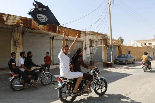 A resident of Tabqa city touring the streets on a motorcycle waves an Islamist flag in celebration after Islamic State militants took over Tabqa air base, in nearby Raqqa city August 24, 2014. REUTERS/Stringer