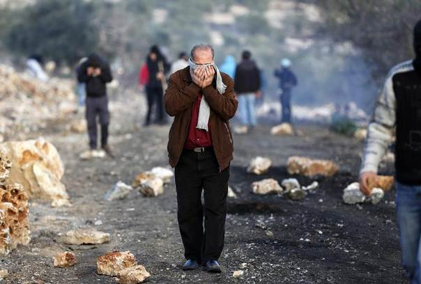 A Palestinian man covers his face to avoid inhaling tear gas fired by Israeli soldiers during clashes with stone-throwing Palestinian protesters after the funeral of Saeed Jaser Ali, in the West Bank village of Kufr Kadum, January 2, 2014. REUTERS/Mohamad Torokman