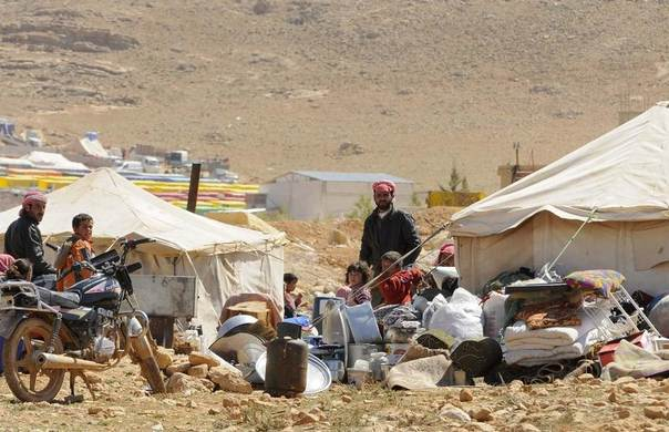 Refugees who fled the violence from the Syrian town of Flita stand outside their tents at the border town of Arsal, in the eastern Bekaa Valley, Lebanon, March 20, 2014. REUTERS/Hassan Abdallah
