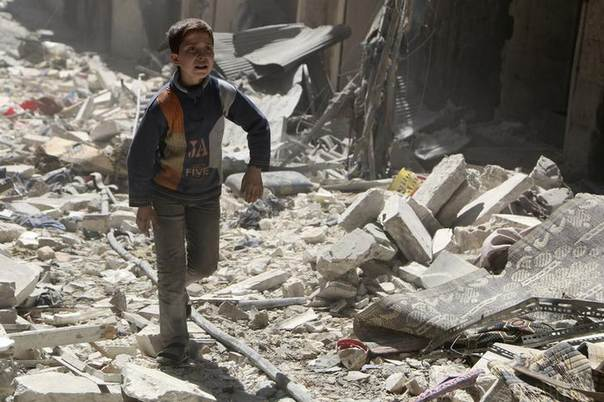 A boy walks on rubble of damaged buildings at a site hit by what activists said was an airstrike by forces loyal to Syria's President Bashar al-Assad in Aleppo's district of al-Sukari March 23, 2014. REUTERS/Hosam Katan