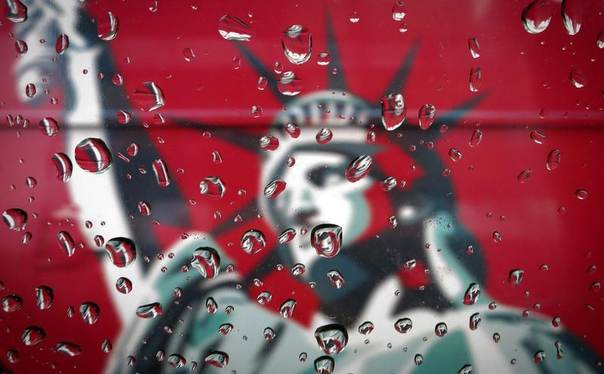An image of the Statue of Liberty is pictured though a rain-covered taxi window in New York, April 15, 2014. REUTERS/Carlo Allegri