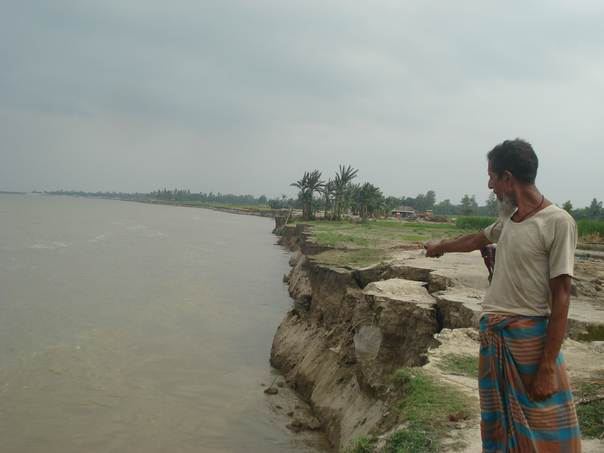 A resident of East Bahuka village in Bangladesh's Sirajganj district shows where land he used to own was lost to growing erosion along the Jamnua River. THOMSON REUTERS FOUNDATION/Syful Islam