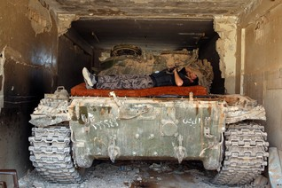 A Free Syrian Army fighter rests on a tank in al-Manshiyeh neighbourhood in Deraa