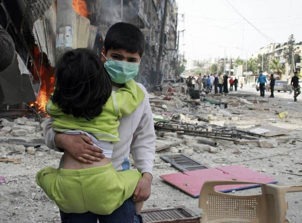 A boy carries a girl after what activists said was an air strike by forces loyal to Syrian President Bashar Al-Assad in Aleppo's Bustan al-Qasr, April 18, 2014. REUTERS/Stringer