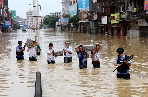People carrying cash boxes walk across a flooded street as they are escorted by the armed security personnel of a cash-in-transit company after Typhoon Utor hit Maoming, Guangzhou province August 15, 2013. REUTERS/Stringer