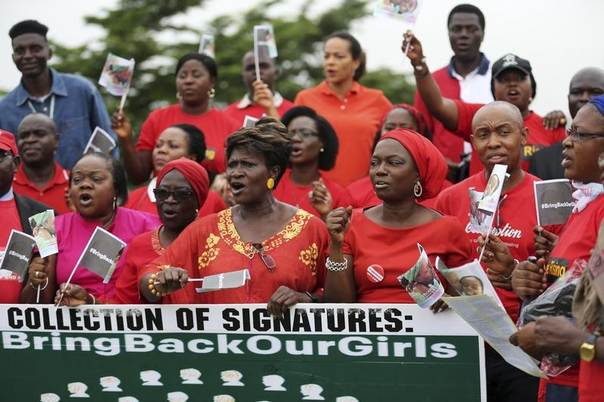 People wearing red holds a banner at a speak-out session of 'bring back our girls' rally in Lagos, Nigeria, June 7, 2014. REUTERS/Akintunde Akinleye