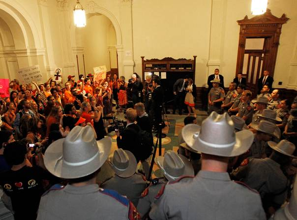 Abortion rights activists (back L) demonstrate as state troopers stand guard outside the Texas House of Representatives in Austin after a bill mandating sweeping abortion restrictions passed on July 9, 2013. REUTERS/Mike Stone