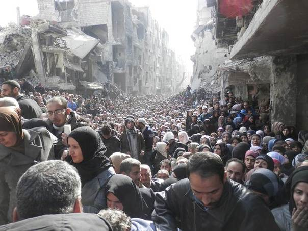 Residents wait to receive food aid distributed by the U.N. Relief and Works Agency (UNRWA) at the besieged al-Yarmouk camp, south of Damascus on January 31, 2014. REUTERS/UNRWA/Handout via Reuters