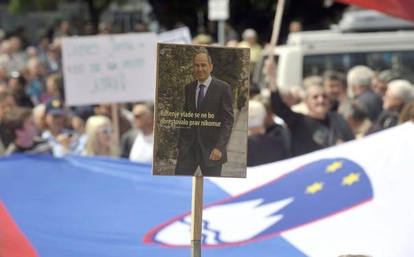 In this 2013 file photo, a supporter of the former Slovenian Prime Minister Janez Jansa holds a placard with Jansa's picture in front of the court during Jansa's corruption trial involving Finnish company Patria in Ljubljana REUTERS/Srdjan Zivulovic