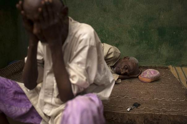 A man rests on a mat as another washes his face prior to prayers near a mosque some distance from Kilometre 12 (PK12) where internally displaced Muslims are stranded due to the ongoing sectarian violence in Bangui March 6, 2014. REUTERS/Siegfried Modola