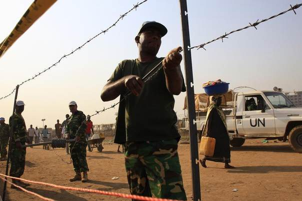 United Nations Mission in South Sudan (UNMISS) personnel erect barbed wire fencing around Tomping camp, where some 15,000 people who fled their homes following recent fighting are sheltered by the United Nations, in Juba, South Sudan, January 7, 2014. REUTERS/James Akena