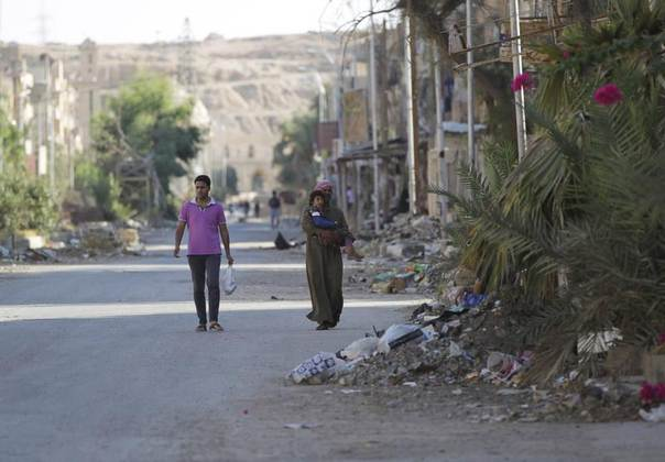 A man holds his child as he walks along a damaged street littered with debris in Deir al-Zor, Syria, July 23, 2013. REUTERS/Khalil Ashawi