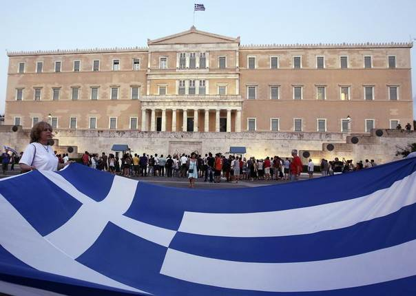 A protester holds a giant Greek national flag in front of the parliament building during a rally against austerity economic measures and corruption in Athens' Syntagma (Constitution) square in this photo from September 2011. REUTERS/John Kolesidis