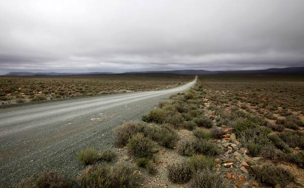 Storm clouds loom as a road cuts through the desolate and arid Karoo landscape near Carnavon in South Africa's Northern Cape province on May 17, 2012. REUTERS/Mike Hutchings