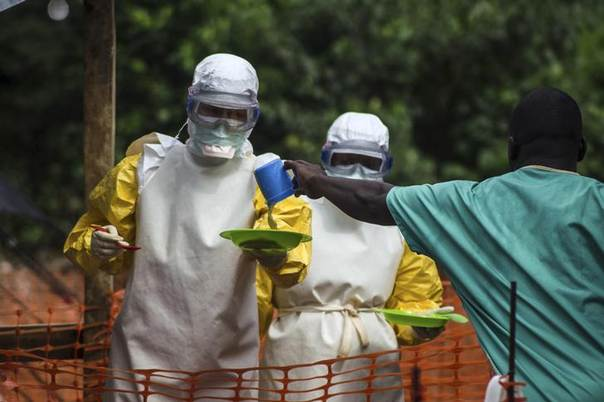 Medical staff working with Medecins sans Frontieres (MSF) prepare to bring food to patients kept in an isolation area at the MSF Ebola treatment centre in Kailahun, Sierra Leone, July 20, 2014. REUTERS/Tommy Trenchard