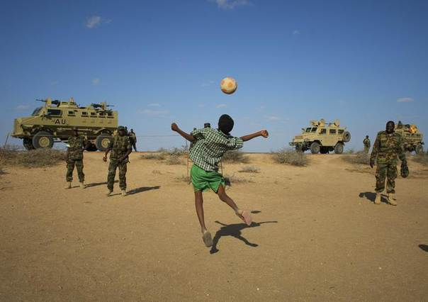 A boy plays soccer with Ugandan soldiers, serving with the African Union Mission in Somalia (AMISOM), in the central Somali town of Buur-Hakba in this picture taken and released by the African Union-United Nations Information Support team on February 28, 2013. REUTERS/AU-UN IST PHOTO/Stuart Price/Handout