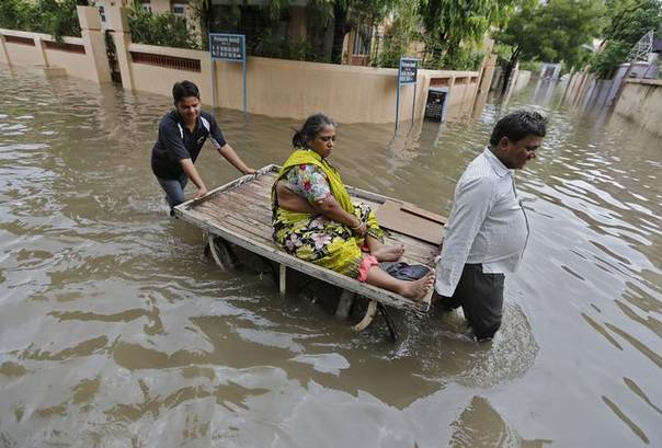 A woman is transported on a handcart through a flooded road after heavy monsoon rains in the western Indian city of Ahmedabad July 30, 2014. REUTERS/Amit Dave