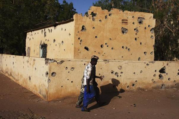 Men walk by a building pockmarked with bullet holes from fighting in Gao March 13 2013. REUTERS/Joe Penney