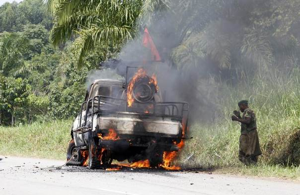 A Congolese soldier from the Armed Forces of the Democratic Republic of Congo (FARDC) stands next to a burning military vehicle after an ambush near the village of Mazizi in North Kivu province January 2, 2014. REUTERS/Kenny Katombe