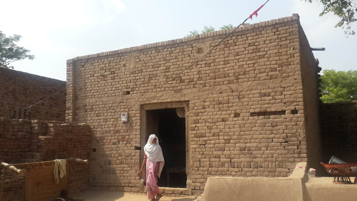 Sonia, the daughter of Ismat Bibi, a 40-year house maid, who has sold her kidney to pay off her debt, comes out of her one-room house in Kot Momin, a dusty town some 220 km south of the Pakistani capital Islamabad on July 9, 2017. Thomson Reuters Foundation / Zeeshan Haider