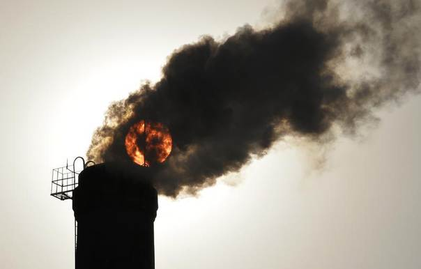 The sun is seen behind smoke billowing from a chimney of a heating plant in Taiyuan, Shanxi province, China, Dec. 9, 2013. REUTERS/Stringer