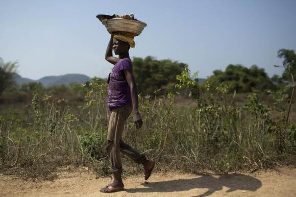 A woman carries her belongings on a dirt road of the outskirts of the capital Bangui March 22, 2014. REUTERS/Siegfried Modola