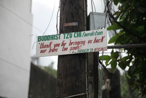 A sign thanking the Tzu Chi Foundation hangs at a street corner in Tacloban, on Jan. 30, 2014. Thomson Reuters Foundation/ Thin Lei Win
