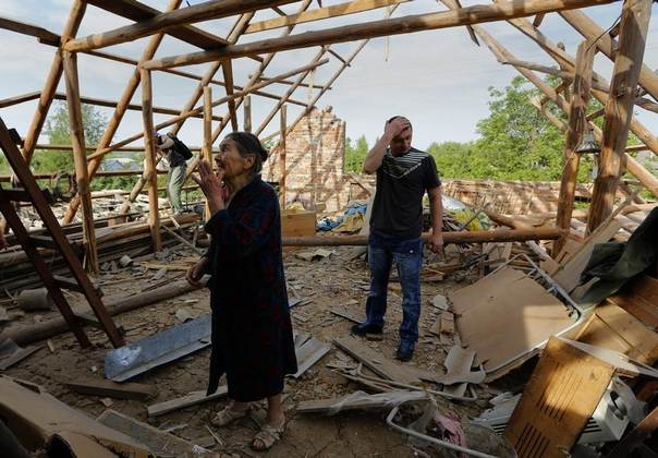 Roza Gerasimenko,79, surveys the damage in her home following what locals say was overnight shelling by Ukrainian forces in the outskirts of the eastern Ukrainian town of Slaviansk, May 20, 2014. REUTERS/Yannis Behrakis
