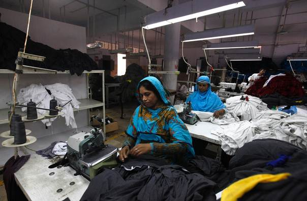 Women workers sew fabrics at garment factory in Karachi