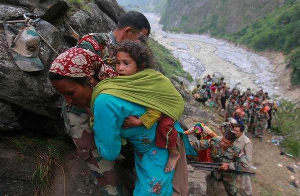 Soldiers assist a woman carrying a child on her back during rescue operations in Govindghat in the Himalayan state of Uttarakhand June 23, 2013. REUTERS/Danish Siddiqui