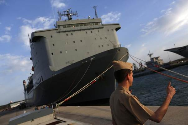 A U.S. navy personnel gestures in front of the U.S. MV Cape Ray ship docked at the naval airbase in Rota, near Cadiz, southern Spain April 10, 2014. Former container vessel Cape Ray, docked in southern Spain, has been fitted out with at least $10 million of gear to let it take on about 560 metric tonnes of Syria's most dangerous chemical agents and sail them out to sea REUTERS/Marcelo del Pozo