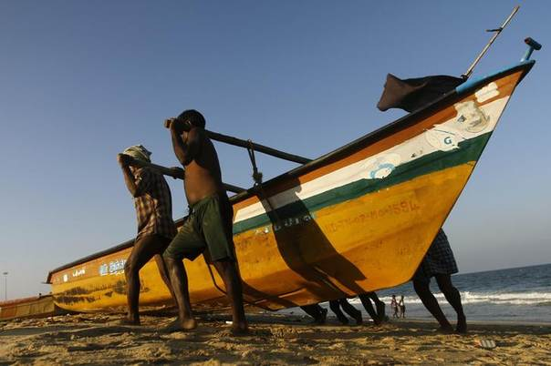 Fishermen pull their fishing boat to the shore after their day's job on Marina beach in the southern Indian city of Chennai March 18, 2014. REUTERS/Babu